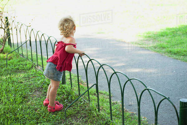 Baby girl standing by fence Royalty-free stock photo