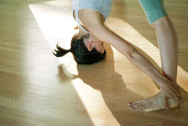 Woman doing standing forward bend yoga pose (Uttanasana) Royalty-free stock photo