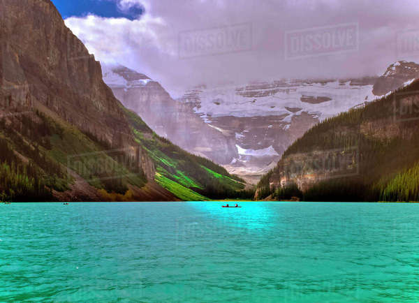 Canoeists bathed in sun on the turquoise waters of Lake Louise in Banff National Park, Alberta, Canada. Royalty-free stock photo