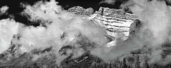 Black and white shot of cloud cover surrounding mountain peaks at Banff National Park, Alberta, Canada. Royalty-free stock photo