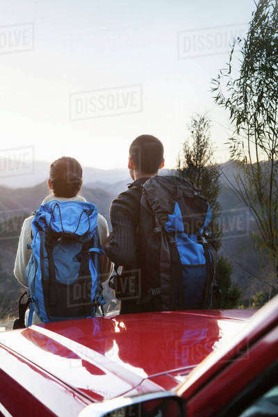 Young couple standing next to the car and looking at the mountains Royalty-free stock photo