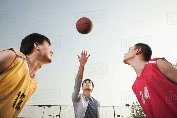 Referee throwing ball in the air, basketball players getting ready for a jump Royalty-free stock photo