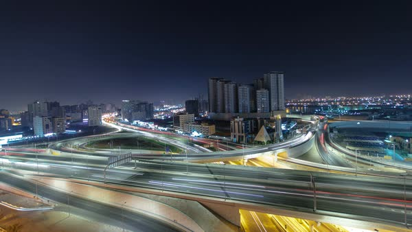 Pan and tilt Cityscape of Ajman with traffic on main road overpass from rooftop at night with lights timelapse fisheye. Royalty-free stock video