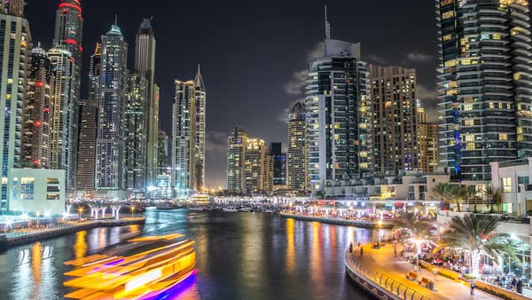 View of Dubai Marina promenade with yachts and modern Towers with restaurants from bridge in Dubai night timelapse hyperlapse, United Arab Emirates. Royalty-free stock video