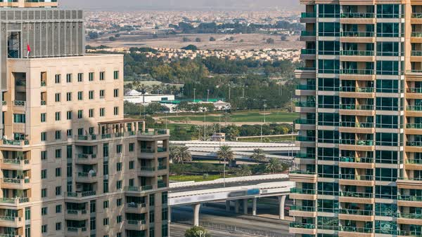 Golf field and Dubai skyline timelapse from top at day time with traffic on sheikh zayed road. Green grass of the golf course against the background the city skyscrapers at sunset. Modern towers on the side Royalty-free stock video