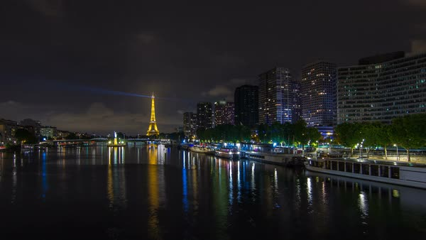 The Statue of Liberty and the Eiffel Tower night Timelapse hyperlapse reflected on water with modern buildings and traffic on road. View from Mirabeau bridge. Paris, France Royalty-free stock video