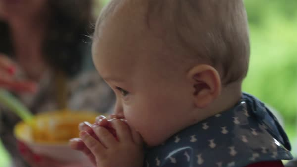 Baby chewing veggie while mom feeds him healthy nutritional baby food Royalty-free stock video