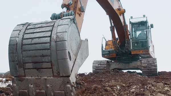 Excavator is digging the frozen ground on a winter day. Royalty-free stock video