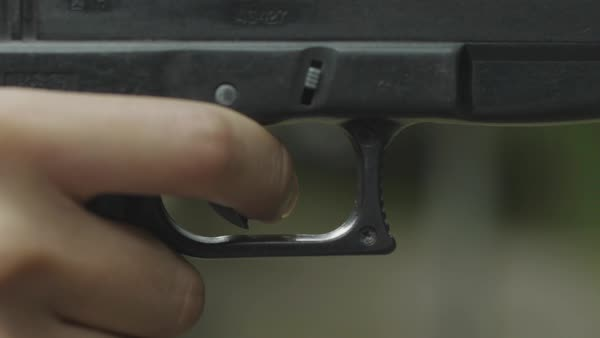 Hand-held shot of a person pulling trigger of a pistol Royalty-free stock video