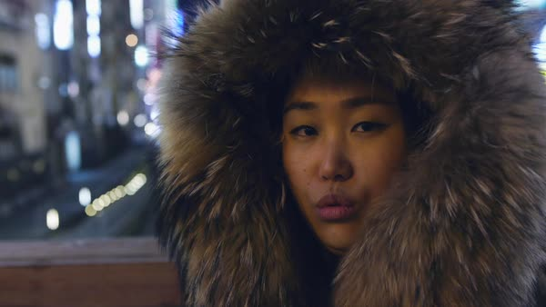 Hand-held shot of a woman wearing a coat with fur hood Royalty-free stock video