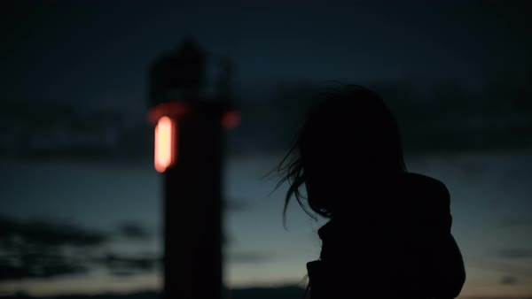Woman's silhouette at the lighthouse on the pier late at night Royalty-free stock video