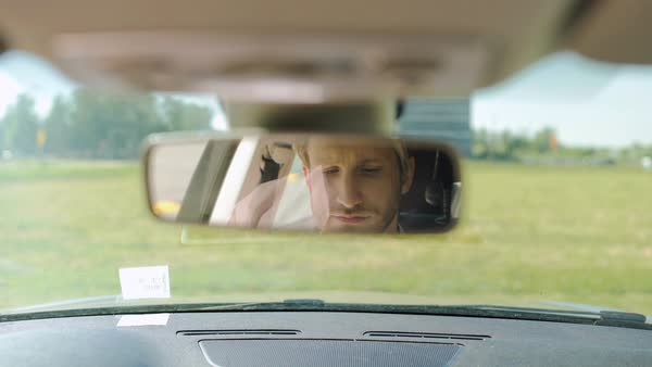 A man is sitting in a car in the parking lot on a summer day and his face is visible in the rearview mirror Royalty-free stock video