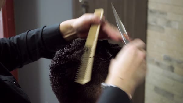 Hairdresser cutting man's hair with scissors and comb Royalty-free stock video