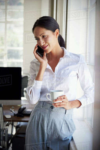Asian businesswoman talking on phone in an office, vertical Royalty-free stock photo