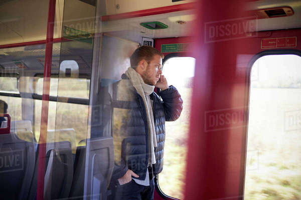 Man standing in train carriage talking on mobile phone Royalty-free stock photo