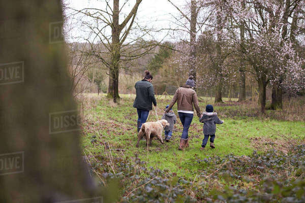 Family on winter walk in countryside with dog together Royalty-free stock photo