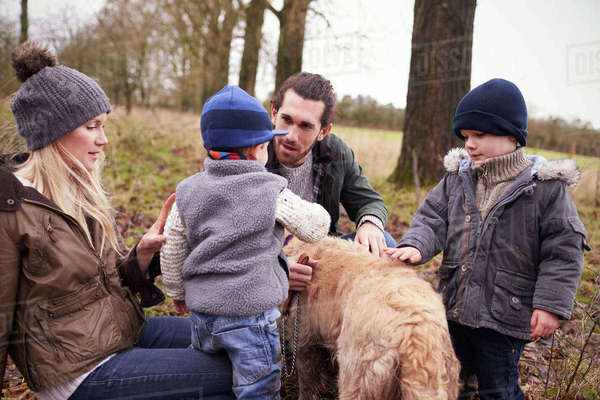 Family with dog on winter walk playing in countryside Royalty-free stock photo