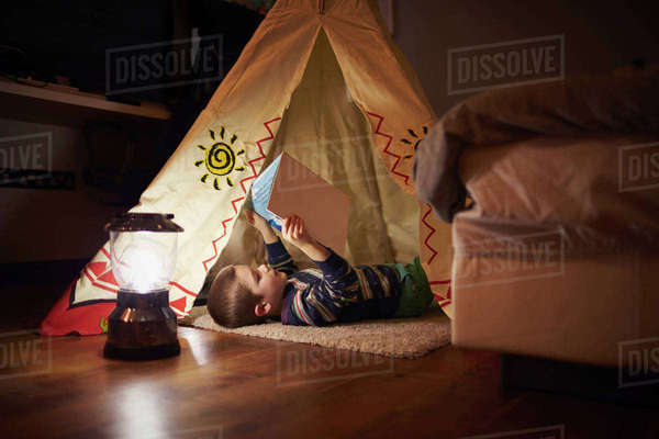 Young boy reading inside tent set up indoors Royalty-free stock photo