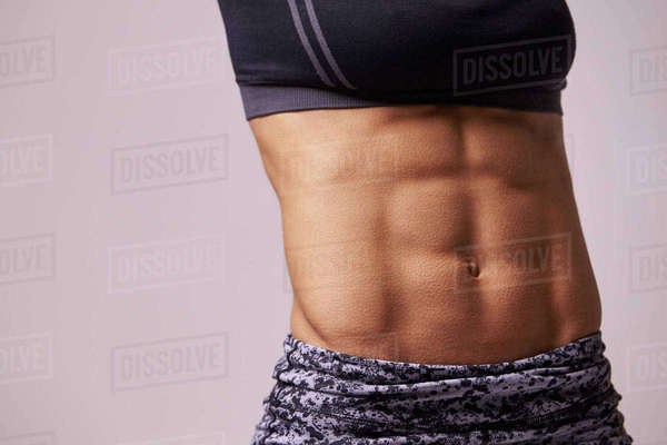 Mid-section crop shot of muscular young woman's abs Royalty-free stock photo