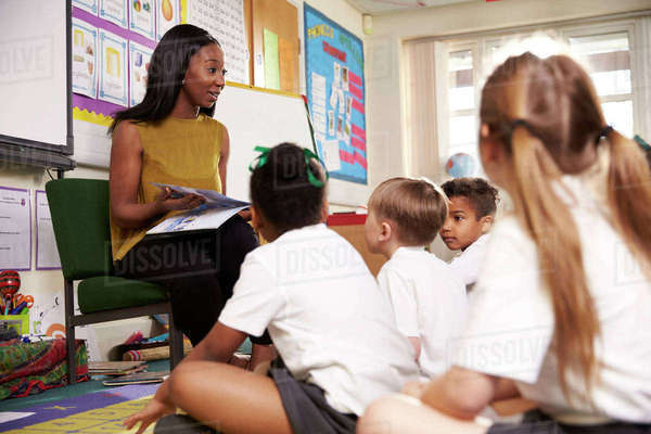 Teacher reading to elementary school pupils in classroom Royalty-free stock photo