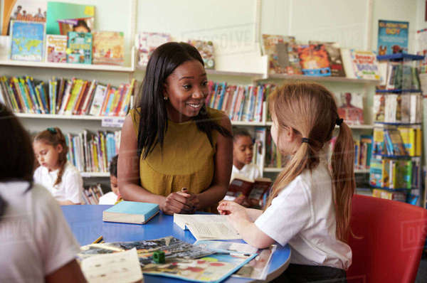 Elementary school pupils reading in library with teacher Royalty-free stock photo