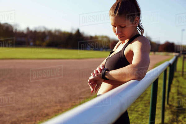 Young Woman Checks Activity Tracker During Outdoor Exercise Royalty-free stock photo