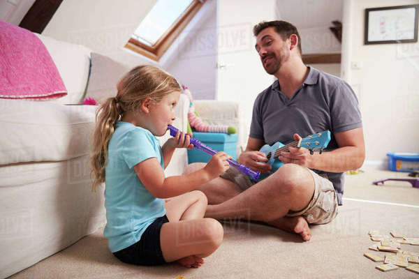 Father And Daughter Playing Ukulele And Recorder Together Royalty-free stock photo