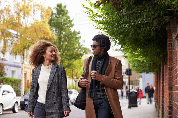 Stylish Young Couple Walking Along Fall Street In City Royalty-free stock photo