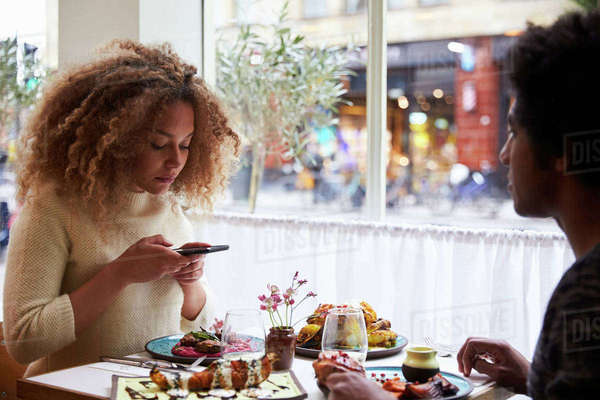 Food Blogger Taking Picture Of Meal In Restaurant On Mobile  Royalty-free stock photo