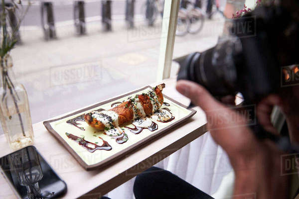 Food Blogger Takes Picture Of Meal In Restaurant With Camera Royalty-free stock photo