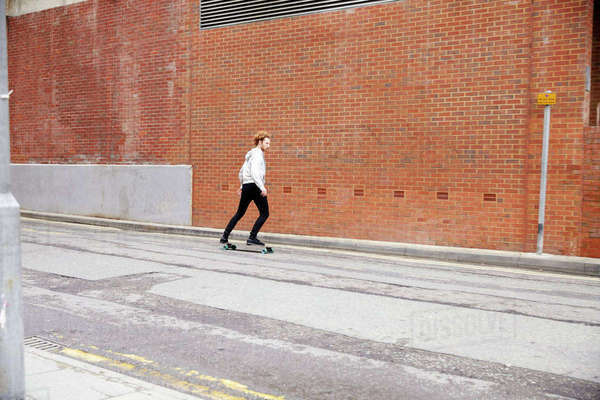 Red haired man skateboarding on an urban road, side view Royalty-free stock photo