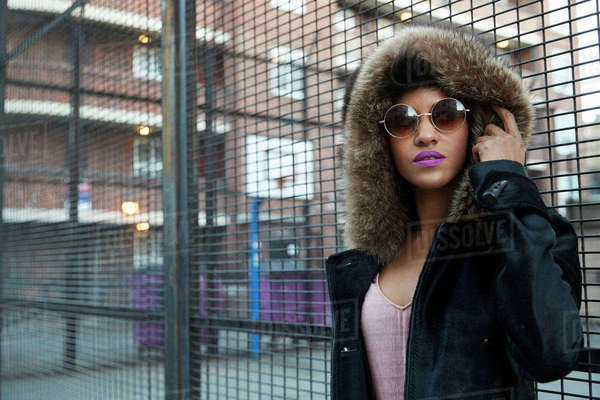 Young woman in fur-lined hood standing by fence, horizontal Royalty-free stock photo