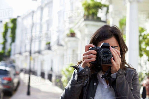 Young woman in street taking photo with SLR camera, close up Royalty-free stock photo