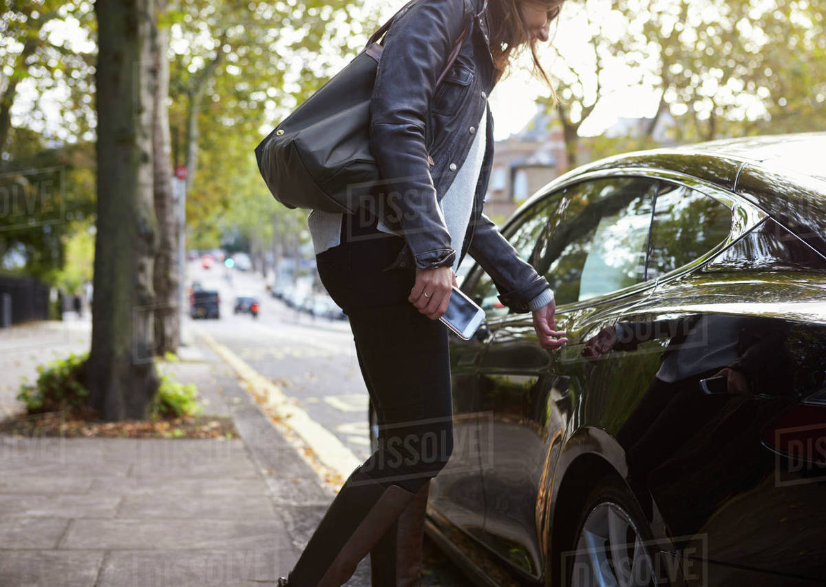 Young woman holding phone getting into the back of a car Royalty-free stock photo