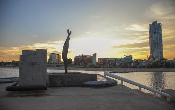 Timelapse of sunset over Barcelona with Capbussament sculpture in foreground Royalty-free stock video