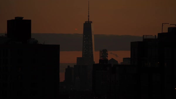 Locked-off shot of One World trade Center in New York City in orange tone sunset Rights-managed stock video