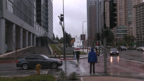 Medium shot of a man in a blue raincoat standing at a busy intersection in West Los Angeles, California Rights-managed stock video