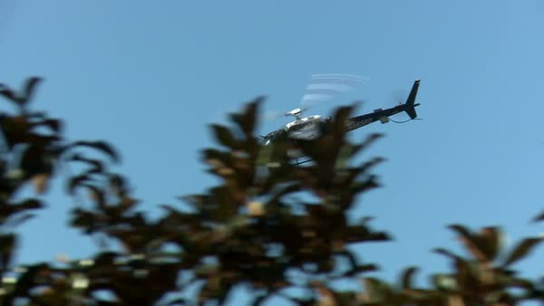 Tracking shot of a police helicopter circling in a clear blue sky Rights-managed stock video