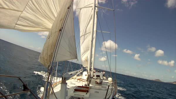Medium oblique shot of a masted sailboat on a windy day on open waters Rights-managed stock video