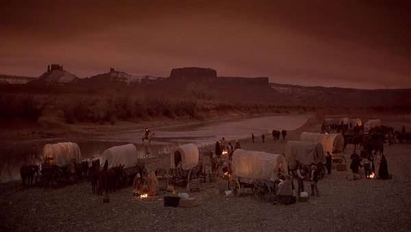 Locked-off shot of 19th-century pioneers with wagons in a desert Rights-managed stock video