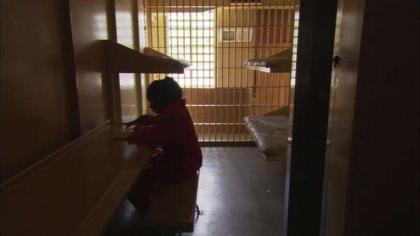 Static shot of a female prisoner reading in her cell Rights-managed stock video
