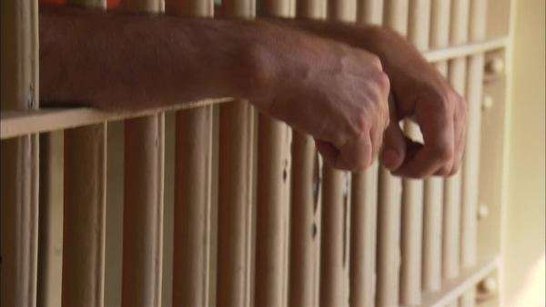 Tilt-up shot of a hands of a prisoner through bars of a cell Rights-managed stock video