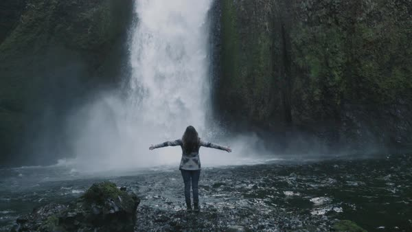 Slow motion shot of a woman standing at a waterfall Royalty-free stock video