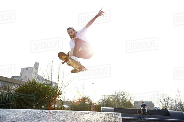 Mid-air action shot of skateboarder in park Royalty-free stock photo