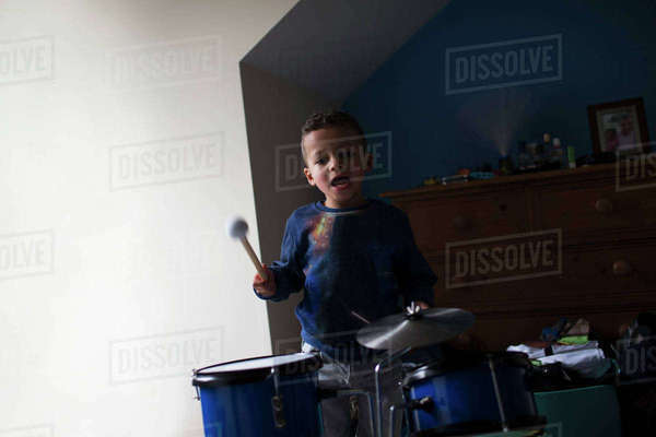 Young boy playing on toy drum kit at home Royalty-free stock photo