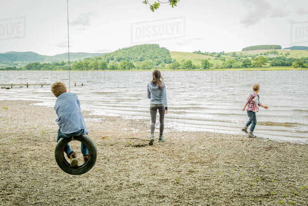 A girl and two boys playing on a tyre hanging from a tree on the shore beside Bala Lake in Wales Royalty-free stock photo