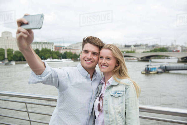 A young couple taking a selfie standing on the Millennium Bridge in London Royalty-free stock photo