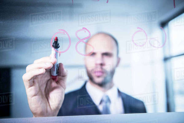 A professional man writing numbers on glass in an office environment Royalty-free stock photo