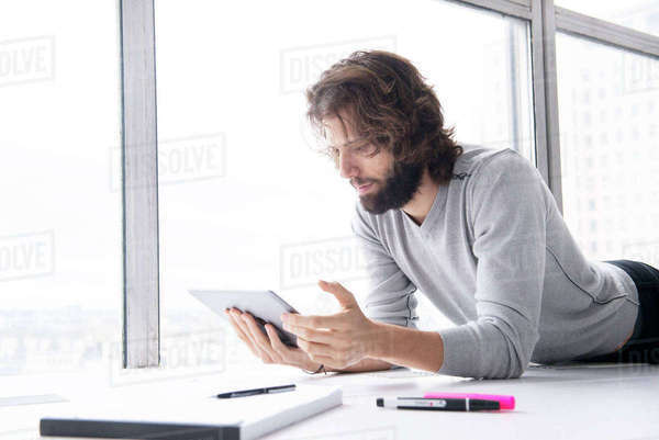 A professional man making notes on a tablet computer in a high rise office environment Royalty-free stock photo