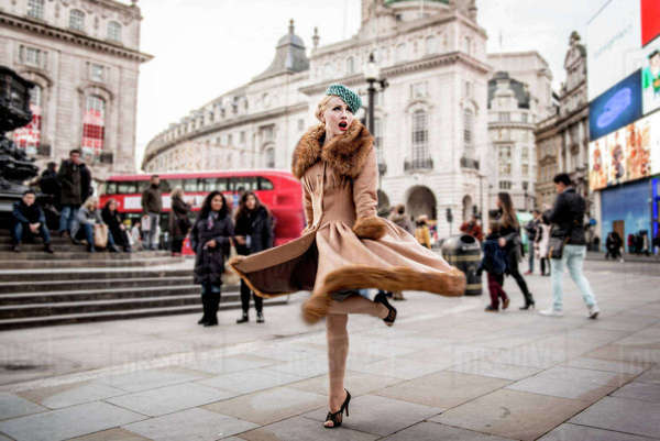 A stylish young woman dressed in 1930s style clothing twirling around by the statue of Eros at Piccadilly Circus Royalty-free stock photo